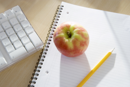 Apple, notepad and pencil on office desk, close-up, elevated view (still life)