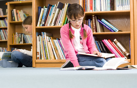 Girl (9-11) and friend reading in library