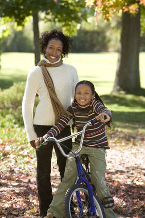 Mother standing with daughter (7-9) in autumn park, girl sitting on bicycle, smiling, portrait