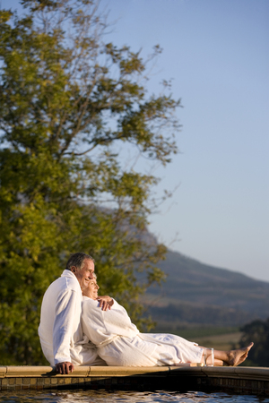 Senior couple wearing white bath robes, embracing outdoors by swimming pool LANG_EVOIMAGES