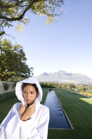 Young woman wearing hooded bath robe outdoors by pool