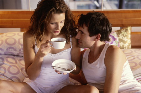 Young couple drinking coffee in bed