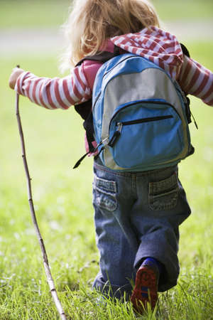 Girl (4-6) hiking on grass, carrying rucksack, holding stick, rear view LANG_EVOIMAGES