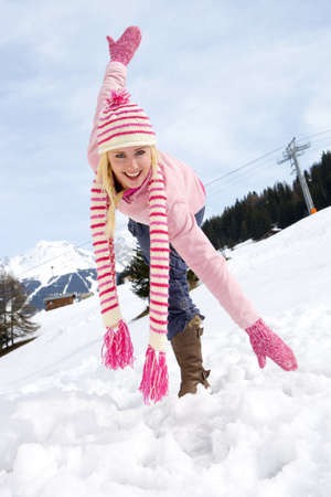 Young woman standing in snow field, wearing woolen hat and scarf, arms outstretched, smiling, portrait LANG_EVOIMAGES