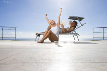 Young woman stretching by man on sun bed on deck by sea, low angle view (lens flare) LANG_EVOIMAGES