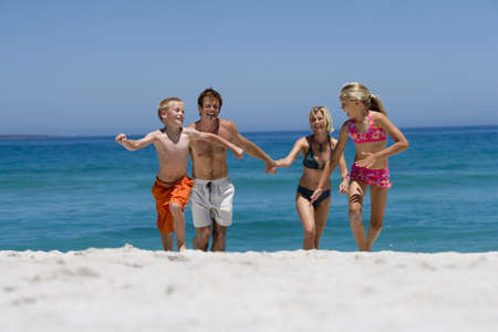 Two generation family in swimwear running from water on beach, smiling, front view LANG_EVOIMAGES