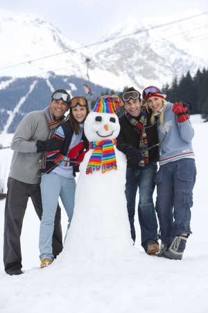 Two young couples standing by snowman in snow field, smiling, portrait, mountain range in background LANG_EVOIMAGES