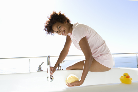 Young woman sitting by bath, smiling, portrait, sea in background