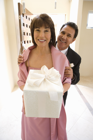 Senior couple, in formalwear, standing in hallway, woman carrying wedding gift, smiling, front view, portrait