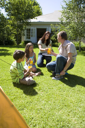 Family taking break from assembling tent on garden lawn, mother serving orange juice, smiling