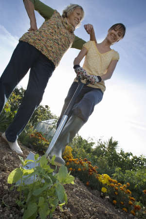 Two women standing with spade in garden, smiling, portrait, low angle view (tilt) LANG_EVOIMAGES