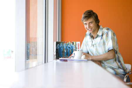 Teenage boy (16-18) sitting in cafe by window with magazine, smiling, portrait