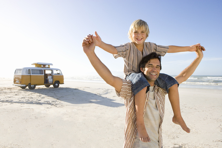 Boy (6-8) on fathers shoulders holding hands on beach, smiling, portrait LANG_EVOIMAGES