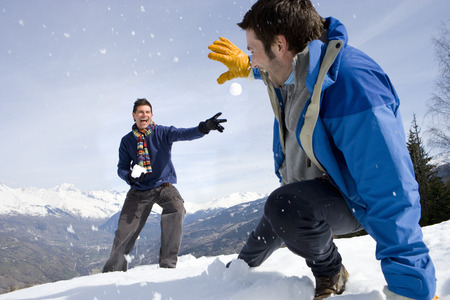 Two young men having snow fight in snow field, smiling