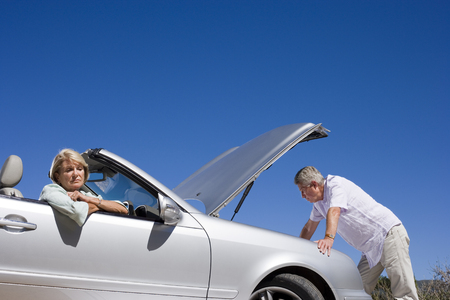 Senior couple experiencing car trouble, sombre woman sitting in passenger seat, man looking at engine LANG_EVOIMAGES