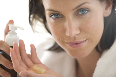 Young woman squeezing cream in hand, portrait, close-up LANG_EVOIMAGES