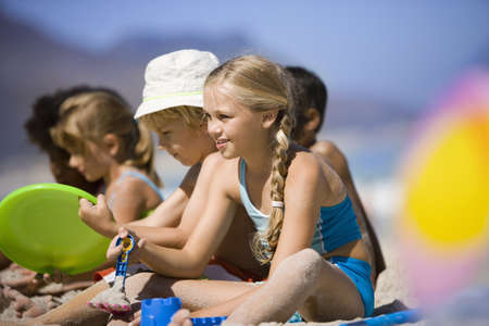 Children (4-9) sitting in line on beach, smiling, side view (differential focus) LANG_EVOIMAGES
