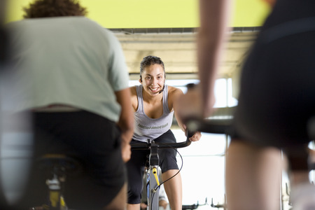 Fitness instructor leading class on exercise bicycles in gym, low angle view LANG_EVOIMAGES