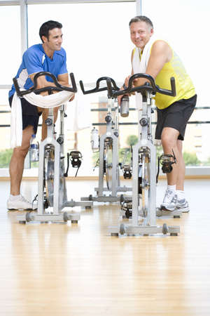 Two men in conversation by exercise bicycles in gym, low angle view LANG_EVOIMAGES