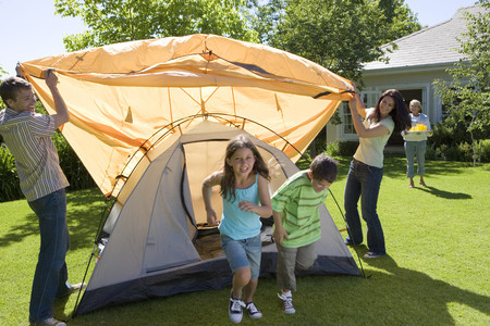 Family assembling orange dome tent on garden lawn, grandmother serving drinks in background, smiling