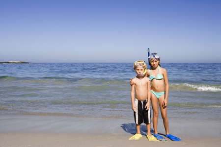 Boy (4-6) and girl (5-7) standing side by side on sandy beach, wearing snorkels and flippers, front view, portrait