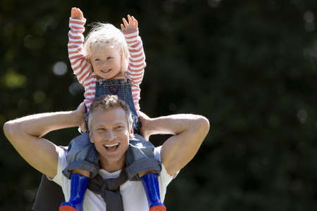 Father carrying daughter (2-3) on shoulders, girl wearing dungarees, striped top and wellington boots, arms up, smiling, front view, portrait LANG_EVOIMAGES