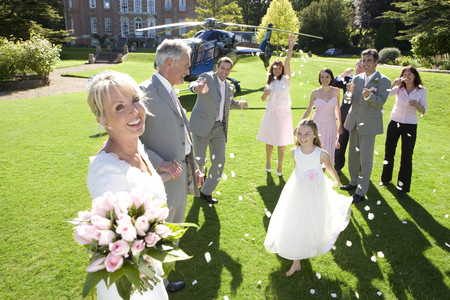 Wedding party throwing confetti on senior bride and groom by helicopter, smiling, portrait of bride