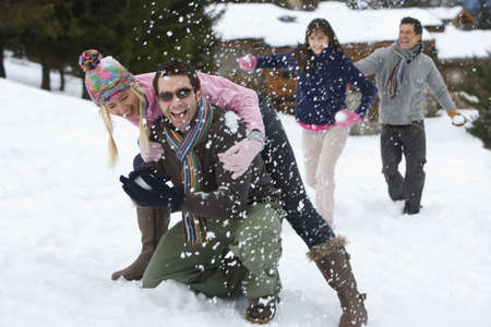 Two young couples having snowball fight in snow field, laughing
