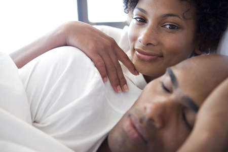 Young couple lying in bed, woman smiling in background, close-up
