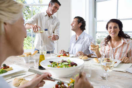 Four friends having lunch at table, man pouring wine, smiling in background