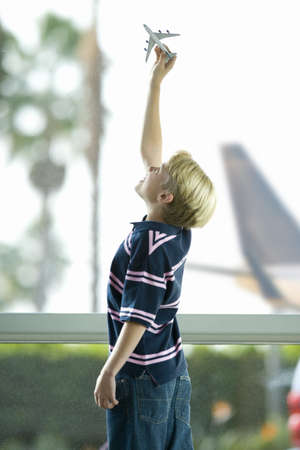 Blonde boy (8-10) playing with toy plane near large window in airport departure lounge, hand raised, profile