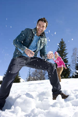 Young couple having snow fight in snow field, smiling, woman in background LANG_EVOIMAGES