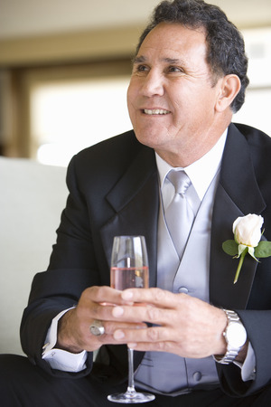 Senior groom, in formalwear, sitting on chair at wedding, holding champagne flute, smiling