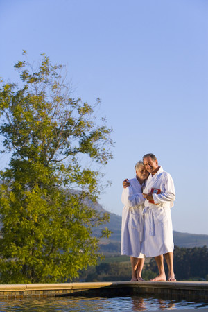 Senior couple wearing white bath robes, embracing outdoors by swimming pool, smiling, portrait