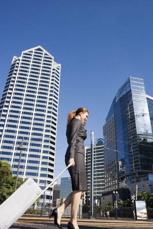 Businesswoman walking with luggage along city street, using mobile phone, profile (surface level) LANG_EVOIMAGES