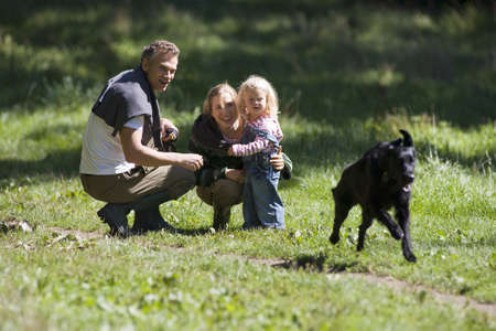 Two generation family watching dog running in field, parents crouching beside girl (2-3)