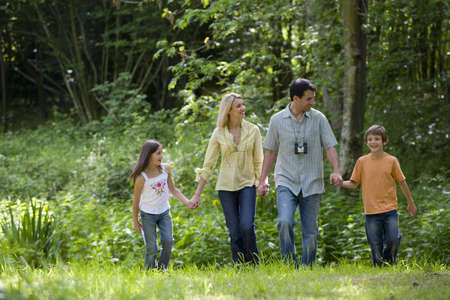 Family of four holding hands in forest, low angle view