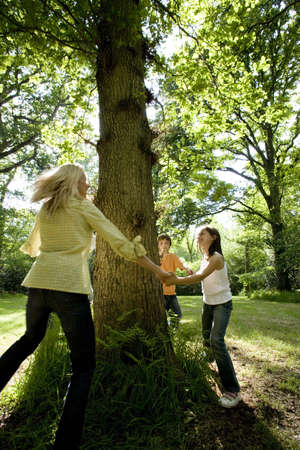 Family of four holding hands around tree in forest (blurred motion)