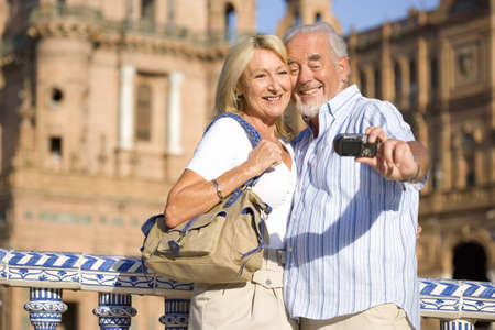 Senior couple taking photograph of themselves by castle, close-up LANG_EVOIMAGES