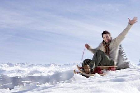Man riding down snow slope on sled, smiling, side view, mountain range in background (blurred motion)