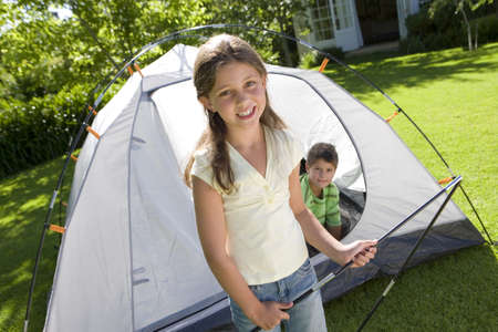 Brother and sister (8-10) assembling dome tent on garden lawn, boy sitting inside tent, girl holding folding tent pole in foreground, smiling, portrait (tilt) LANG_EVOIMAGES