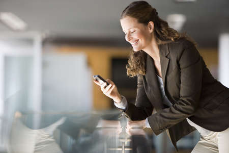 Businesswoman leaning on glass table, reading text message on mobile phone, smiling, side view