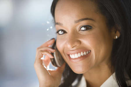 Businesswoman using mobile phone, smiling, side view, close-up, portrait