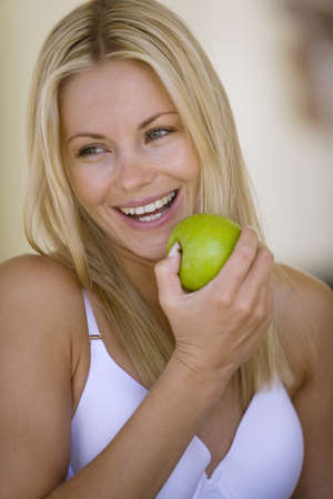 Young woman in underwear with apple, smiling, close-up LANG_EVOIMAGES
