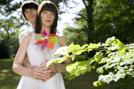 Young couple outdoors, man embracing woman, woman with pinwheel, portrait, low angle view