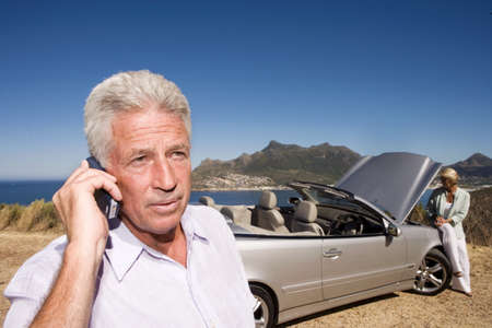 South Africa, Cape Town, mature man using mobile phone by sea, woman by car in background
