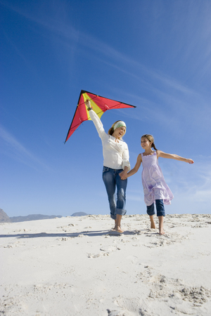 Mother and daughter (5-7) with kite on beach, smiling, low angle view LANG_EVOIMAGES