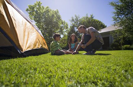 Father hammering tent peg into garden lawn, two children (8-10) assisting, smiling, side view (surface level)