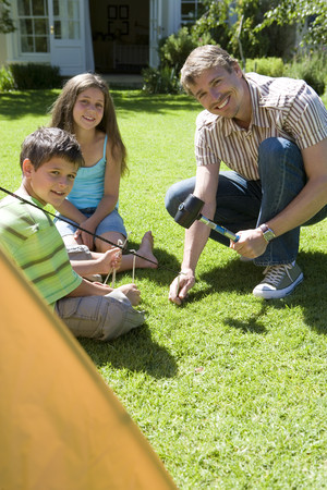 Father hammering tent peg into garden lawn, two children (8-10) assisting, smiling, portrait LANG_EVOIMAGES