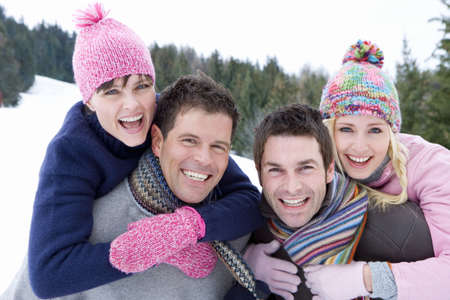 Two young couples smiling in snow field, portrait, men carrying women on backs, close-up LANG_EVOIMAGES